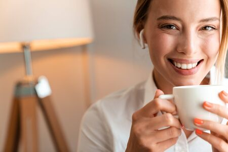 Image of a young cheerful happy blonde business woman sit indoors in cafe drinking coffee using wireless bluetooth earphones.