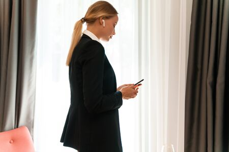 Photo of a young pretty beautiful blonde business woman indoors using mobile phone listening music with earphones.