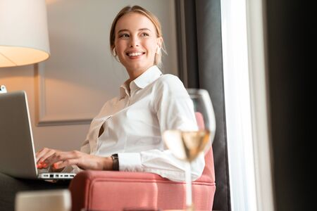 Image of a young beautiful happy smiling blonde business woman sit indoors in cafe using laptop computer. Reklamní fotografie