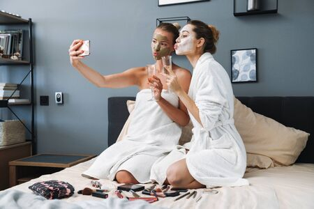 Photo of a cute beautiful women at home in towel and bathrobe after spa procedure taking care of their skin with face mask sit on bed drinking champagne blowing kisses take selfie by mobile phone.