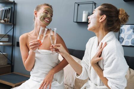 Image of a laughing positive young women friends sisters at home in towel and bathrobe after spa procedure taking care of their skin with face mask sit on bed drinking champagne.