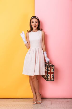 Full length of a beautiful young elegant brunette woman wearing dress and gloves standing isolated over double color background, carrying suitcase