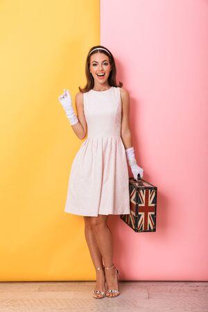 Longitud total de una joven y bella mujer morena elegante con vestido y guantes que se encuentran aisladas sobre fondo de doble color, llevando maleta