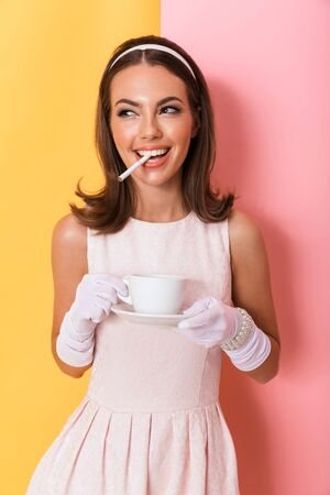Beautiful smiling young elegant brunette woman wearing dress and gloves standing isolated over double color background, having cup of coffee with cigarette Stockfoto