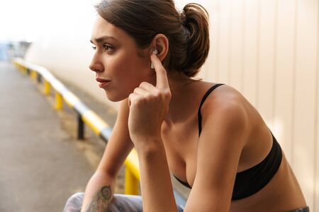 Image of charming young woman in sportswear listening music with earpod while sitting on parking outdoors