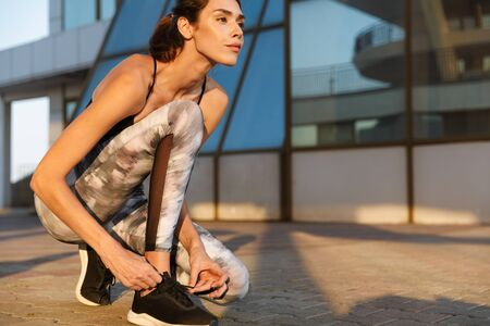 Image of confident pleased woman in sportswear tying her shoelaces while working out near glass building in morning