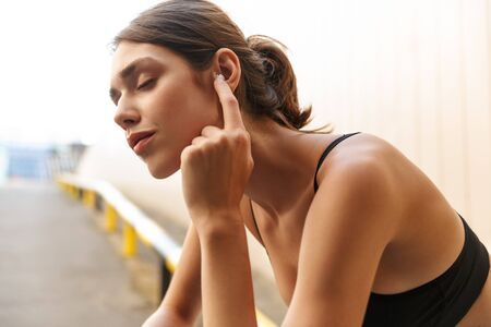 Image of relaxed young woman in sportswear listening music with earpod while sitting on parking outdoors