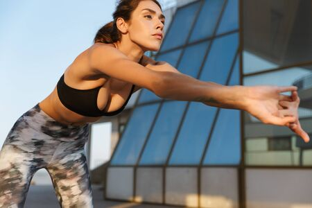 Image of confident focused woman in sportswear doing exercise while working out near glass building in morning