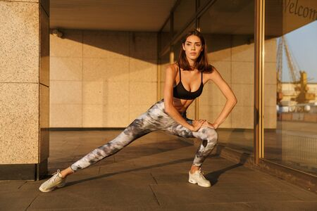 Image of caucasian slim woman in sportswear doing exercise while working out near building in morning