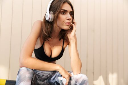 Image of focused charming woman in sportswear listening music with headphones while sitting on parking outdoors