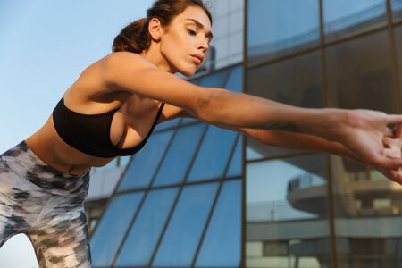 Image of confident slim woman in sportswear doing exercise while working out near glass building in morning