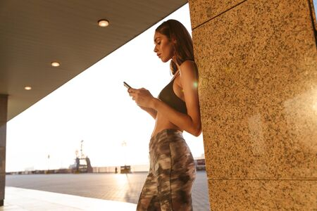 Image of young satisfied woman in sportswear typing on cellphone while working out near building in morning