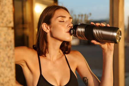 Image closeup of young slim woman in sportswear drinking water from bottle while working out near building in morning