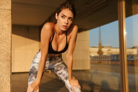 Image of caucasian young woman in sportswear resting while working out near building in morning
