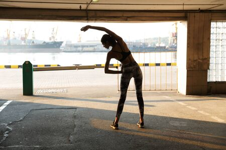 Image of caucasian slim woman in sportswear doing exercise while working out on parking near seaport 스톡 콘텐츠