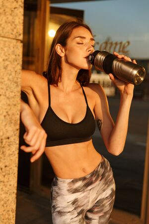 Image of young slim woman in sportswear drinking water from bottle while working out near building in morning