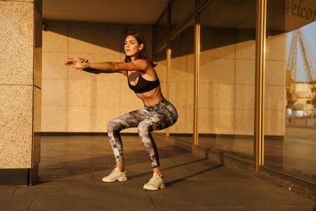 Image of focused slim woman in sportswear doing exercise while working out near building in morning