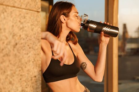 Image of young attractive woman in sportswear drinking water from bottle while working out near building in morning