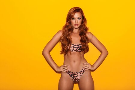 Photo of young ginger woman wearing leopard bikini looking at camera and holding hands on waist isolated over multicolor background