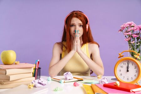 Photo of disappointed student girl sitting at desk with exercise books while doing homework isolated over purple background