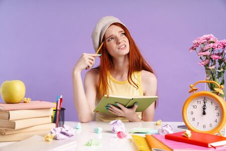 Photo of confused student girl writing in exercise book while doing homework isolated over purple background Banco de Imagens
