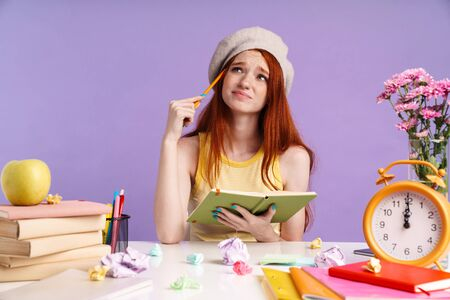 Photo of frustrated student girl writing in exercise book while doing homework isolated over purple background