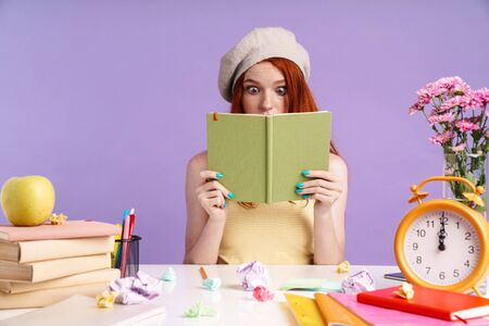 Photo of confused student girl holding exercise book while doing homework isolated over purple background