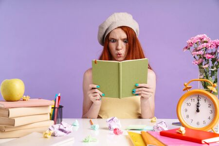 Photo of puzzled student girl holding exercise book while doing homework isolated over purple background Banco de Imagens
