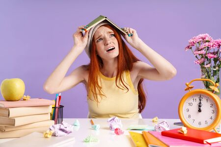 Photo of confused student girl holding exercise book on her head while doing homework isolated over purple background