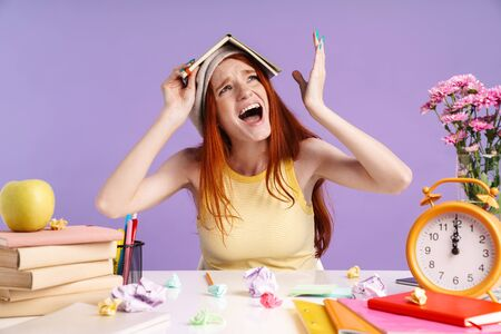 Photo of nervous student girl holding exercise book on her head while doing homework isolated over purple background Banco de Imagens