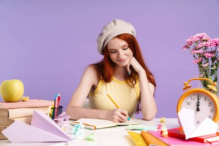 Photo of pretty student girl writing in exercise book while doing homework isolated over purple background
