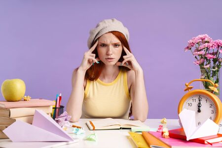 Photo of confused student girl touching her temples while doing homework isolated over purple background