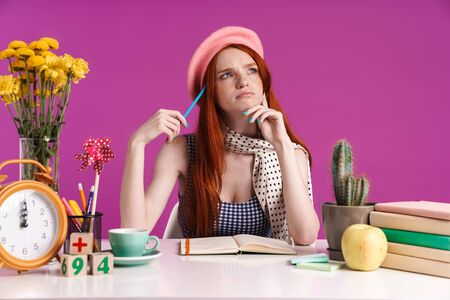 Image of thoughtful teenage girl studying with exercise books while sitting at desk isolated over violet background