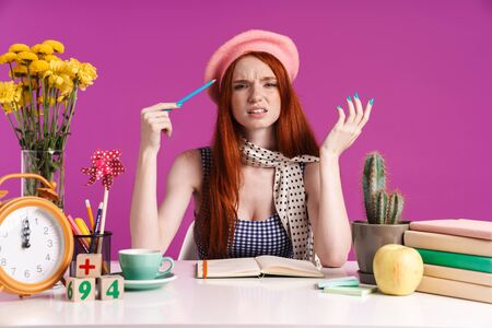 Image of puzzled teenage girl studying with exercise books while sitting at desk isolated over violet background Banco de Imagens