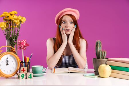 Image of shocked teenage girl grabbing her face while studying with exercise books isolated over violet background