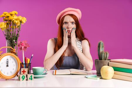 Image of stressed teenage girl grabbing her face while studying with exercise books isolated over violet background