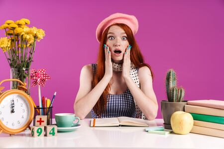 Image of scared teenage girl grabbing her face while studying with exercise books isolated over violet background