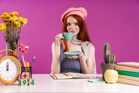 Image of gorgeous teenage girl drinking cup of tea while studying with exercise books at desk isolated over violet background 스톡 콘텐츠