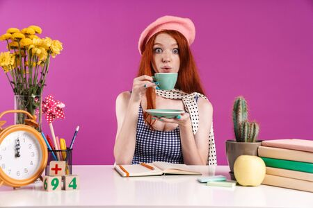 Image of redhead teenage girl drinking cup of tea while studying with exercise books at desk isolated over violet background 스톡 콘텐츠