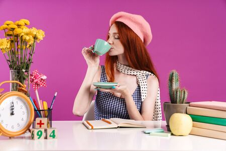 Image of caucasian teenage girl drinking cup of tea while studying with exercise books at desk isolated over violet background