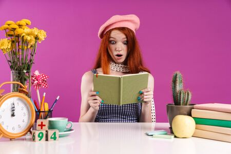 Image of young student girl holding diary book while sitting at desk isolated over violet background