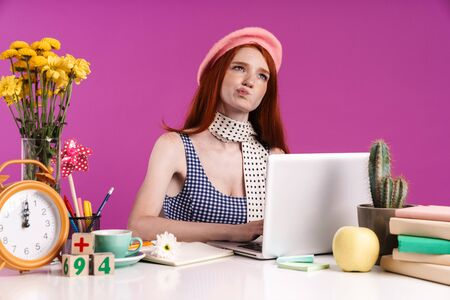Image of thoughtful teen girl studying on laptop computer while sitting at desk isolated over violet background