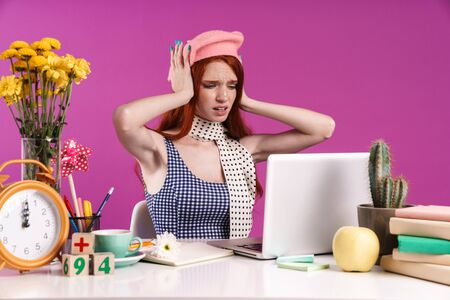 Image of stressed teen girl studying on laptop computer while sitting at desk isolated over violet background Banco de Imagens
