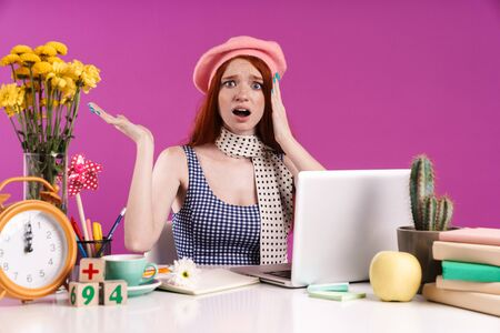 Image of frustrated teen girl studying on laptop computer while sitting at desk isolated over violet background
