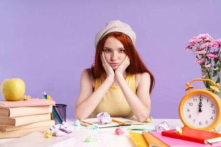 Photo of upset student girl sitting at desk with exercise books while doing homework isolated over purple background Banco de Imagens