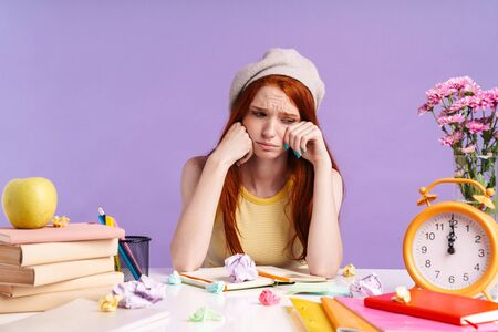Photo of crying student girl sitting at desk with exercise books while doing homework isolated over purple background Banco de Imagens