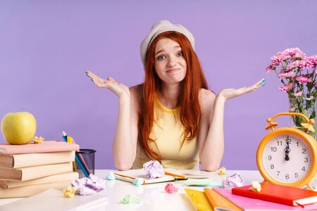 Photo of puzzled student girl throwing up hands while sitting at desk with exercise books isolated over purple background