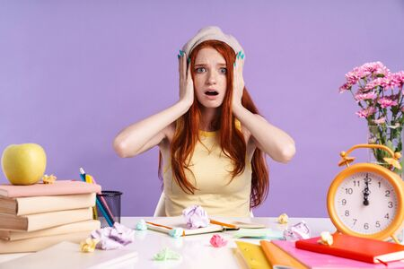 Photo of disappointed student girl grabbing her head while sitting at desk with exercise books isolated over purple background
