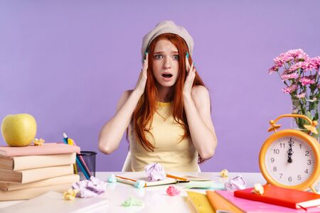 Photo of shocked student girl grabbing her head while sitting at desk with exercise books isolated over purple background Banco de Imagens