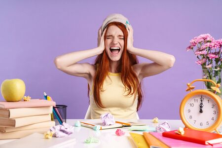 Photo of screaming student girl grabbing her head while sitting at desk with exercise books isolated over purple background Banco de Imagens